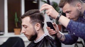 Barbeiro e cliente masculinos Cabeleireiro que faz o penteado com tosquiadeira Cena da barbearia video estoque
