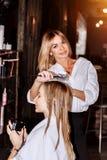 Barbeiro louro de sorriso bonito com seu cliente no cabeleireiro Cuidado, profissão, cosmetologia, termas, salão de beleza foto de stock