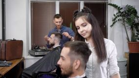Barbeiro masculino que trabalha com o cliente coberto com o cabo do corte que dá forma perfeitamente a seu corte de cabelo com pe video estoque
