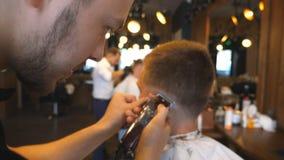 Barbeiro profissional que corta o cabelo do indivíduo com a lâmina elétrica no barbeiro Cabeleireiro que faz o corte de cabelo ma vídeos de arquivo