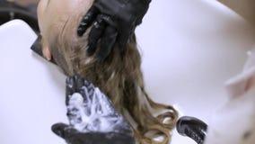 Barbeiro que aplica o condicionador ou a queratina antes de fazer um penteado filme