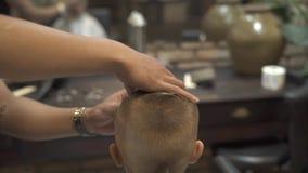 Barbeiro que barbeia com lâmina reta quando corte de cabelo das crianças no salão de beleza Barbeando o cabelo com a lâmina ao ra filme
