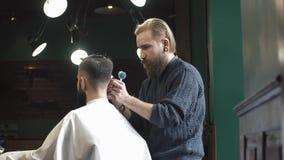 Barbeiro que barbeia o cabelo no barbeiro video estoque