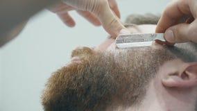 Barbeiro que barbeia o homem com lâmina video estoque