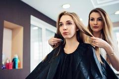 Barbeiro que decide com o cliente fêmea novo que corte de cabelo a fazer na sala de estar do cabeleireiro Dois louros bonitos Imagem de Stock Royalty Free