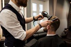 Barbeiro que denomina o cabelo do cliente com secador foto de stock