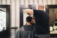 Barbeiro que faz o corte de cabelo dos homens a um homem atrativo Imagens de Stock