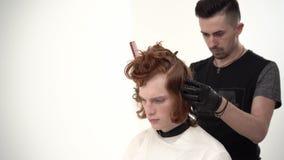 Barbeiro que guarda um pente e para scissor perfoming um corte de cabelo para um cliente do gengibre video estoque