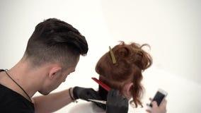Barbeiro que guarda um pente e para scissor perfoming um corte de cabelo para um cliente do gengibre vídeos de arquivo