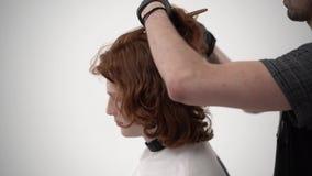 Barbeiro que guarda um pente e para scissor perfoming um corte de cabelo para um cliente do gengibre filme