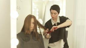 Barbeiro que penteia e que corta o cabelo longo com as tesouras no salão de beleza do cabeleireiro Feche acima do cabeleireiro qu vídeos de arquivo