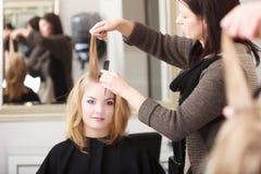 Barbeiro que penteia a menina loura do cliente fêmea no salão de beleza do cabeleireiro Fotografia de Stock
