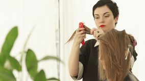 Barbeiro que penteia o cabelo fêmea durante o corte no salão de beleza do cabeleireiro Feche acima do cabeleireiro que faz o cort vídeos de arquivo