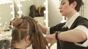Barbeiro que penteia o cabelo fêmea durante haircutting no salão de beleza do cabeleireiro Feche acima do penteado da mulher no s video estoque