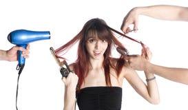 Barbeiros que denominam o cabelo de uma jovem mulher fotografia de stock