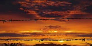 Barbelé au coucher du soleil rouge Image libre de droits