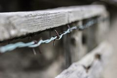 Barbelé rouillé sur une barrière en bois image libre de droits