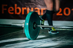 Barbel deadlift on a wooden floor. Athlete of powerlifter is preparing to attempt royalty free stock photography