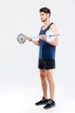 Barbell de ejercicio y de elevación del atleta serio del hombre joven Imagen de archivo libre de regalías