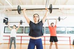 Barbell de elevación femenino fuerte en club de salud imagen de archivo