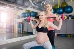 Barbell de levage heureux de femme enceinte avec son entraîneur personnel images libres de droits