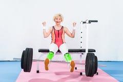 barbell de levage de sportive supérieure heureuse avec des jambes et le sourire photographie stock libre de droits