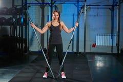 Barbell de levantamento da mulher bonita da aptidão Levantar peso desportivo da mulher Menina apta que exercita os músculos da co Imagem de Stock