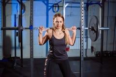 Barbell de levantamento da mulher bonita da aptidão Levantar peso desportivo da mulher Menina apta que exercita os músculos da co Imagem de Stock Royalty Free