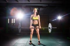 Barbell de levantamento da mulher forte como uma parte da rotina do exercício do crossfit Jovem mulher apta que levanta pesos pes fotos de stock