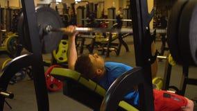 Barbell de levantamento do atleta do homem no banco video estoque