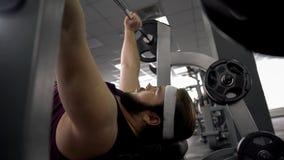 Barbell de levantamento do gym do homem gordo decidido, encontrando-se no banco, programa do exercício do corpo fotografia de stock