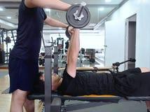 Barbell de levantamento do homem asiático novo saudável com o instrutor pessoal no gym do esporte Conceito da aptidão e do exercí fotos de stock
