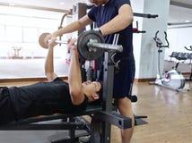 Barbell de levantamento do homem asiático novo saudável com o instrutor pessoal no gym do esporte Conceito da aptidão e do exercí imagem de stock