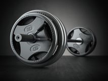 Barbell on floor in black background. Fitness and bodybuilding. Royalty Free Stock Photo