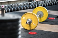 Barbell on the floor in gym. Yellow barbell on the floor in gym, viewed from the side in selective focus. Heavy weights training equipment royalty free stock photography