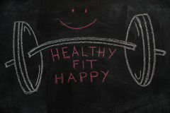 Barbell and healthy, fit, happy words on black chalkboard