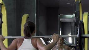 Barbell hermoso de Is Training With A del modelo de la aptitud de la mujer joven almacen de metraje de vídeo