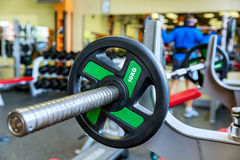 Barbell holder in gym. Barbell holder in the gym. On the rear background man, working out with barbell stock photos