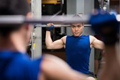 Barbell. Man lifting barbell in front of the mirror royalty free stock photography