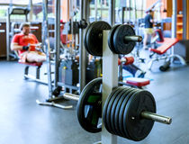 Barbell plates holder in gym. Barbell plates holder rack in the gym. On the rear background man, working out with barbell royalty free stock photo