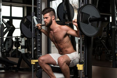 Barbell Squat. Young Man Performing Barbell Squats - One Of The Best Bodybuilding Exercise For Legs Royalty Free Stock Photos