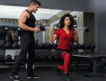 Personal instructor helping woman with barbell squats royalty free stock images