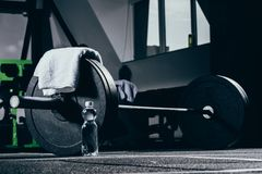 Barbell, towel and bottle of water on floor. In gym royalty free stock photography