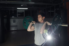 Barbell voor hurkende oefening - atletische mens tijdens intense training bij de gymnastiek Royalty-vrije Stock Afbeeldingen
