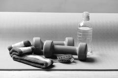 Barbells δίπλα στο ρόλο του μέτρου ταινιών Αλτήρες, μπουκάλι νερό στοκ φωτογραφίες με δικαίωμα ελεύθερης χρήσης