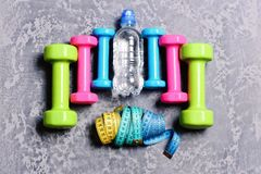 Barbells, ζωηρόχρωμα μέτρα ταινιών και μπουκάλι νερό που τοποθετούνται στο σχέδιο στοκ φωτογραφίες με δικαίωμα ελεύθερης χρήσης