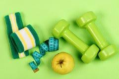 Barbells, μήλο και ταινία μέτρου κοντά στην πράσινη ζώνη χεριών στοκ φωτογραφία με δικαίωμα ελεύθερης χρήσης