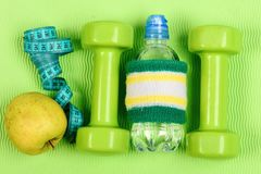 Barbells, μήλο, ταινία και μπουκάλι νερό με την πράσινη ζώνη χεριών στοκ εικόνες