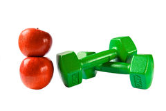 Barbells and apples. Two green barbells and two red apples stock photos