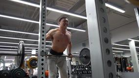 Barbells de elevación del hombre descamisado apto en gimnasio metrajes